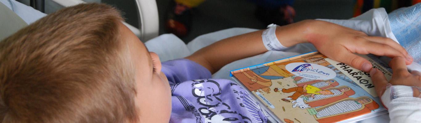 Petit garçon hospitalisé ayant reçu une bande dessinée en cadeau