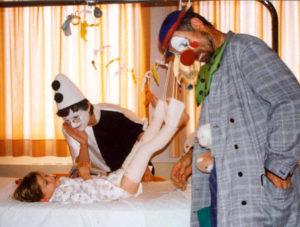 2 hopiclowns jouant avec un enfant malade sur son lit